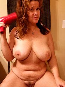 Голая зрелая дамочка сушит волосы