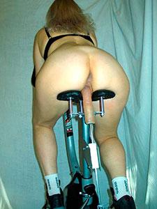 Женщина на велотренажере с дилдо